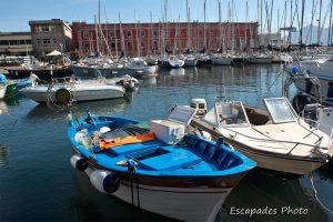 Bateau de pêche devant le bâtiment de la Marine italienne